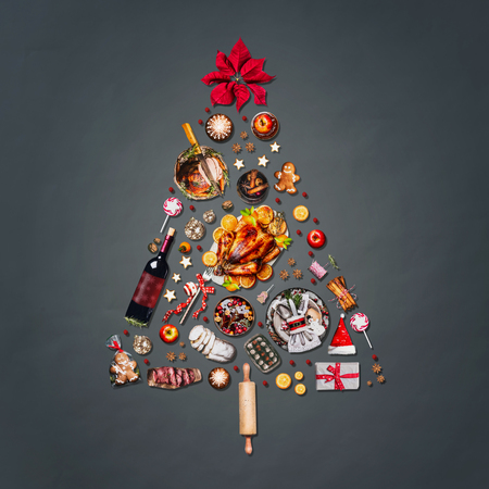 Christmas tree made with various Christmas food: turkey on platter, roasted ham, sweets and candies, cookies , mulled wine, gingerbread  man decorated with gift box and poinsettia on gray background Stock Photo