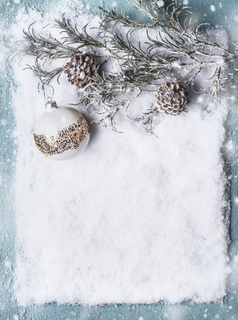 Christmas background  with white gold bauble , frozen branches and cones on snow with snowfall, top view with copy space for your design, frame