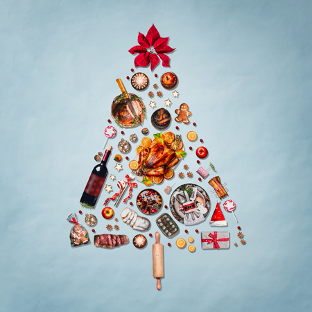 Christmas tree made with various Christmas food: turkey on platter, roasted ham, sweets and candies, cookies , mulled wine, gingerbread  man decorated with gift box and poinsettia on blue background