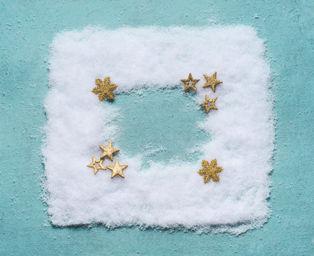 Christmas background frame made with snow on blue background with golden stars decoration, top view, flat lay. Winter composition and holiday concept