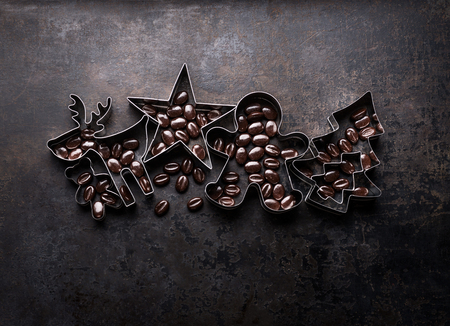 Christmas cookies cutters - Christmas tree,  deer, star, gingerbread mann shape with cocoa beans on dark rustic background, top view Standard-Bild - 113758649