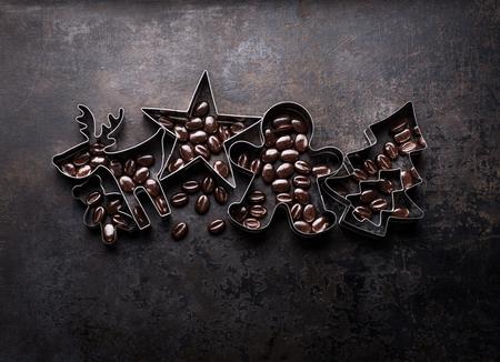 Tagliabiscotti di Natale - albero di Natale, cervo, stella, forma di mann di pan di zenzero con fave di cacao su fondo rustico scuro, vista dall'alto