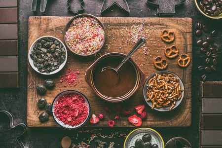 Homemade chocolate bars making. Various toppings and flavorings ingredients in bowls with melted chocolate on dark rustic kitchen table background, top view. Clean eating.  Edible Christmas gifts Фото со стока