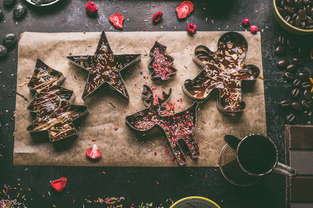 Homemade Christmas chocolate bars making. Christmas cutters with various toppings and flavorings filled with melted chocolate and caramel on dark rustic kitchen table background, top view Фото со стока
