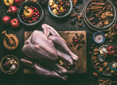 Raw whole turkey stuffed with dried fruits and apples on wooden cutting board, dark kitchen table background with ingredients , top view. Cooking preparation for Thanksgiving or Christmas dinner. Фото со стока - 113758656