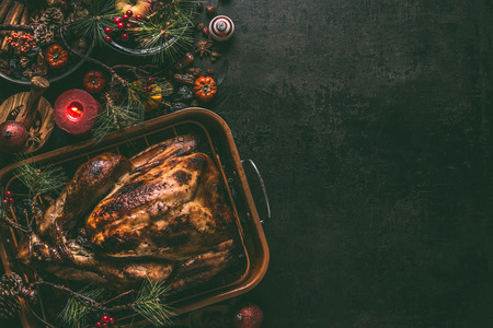 Whole roasted turkey, stuffed with dried fruits in roasting pan for Christmas dinner, served on dark table background with decoration and burning candles,  top view with copy space for your design 版權商用圖片