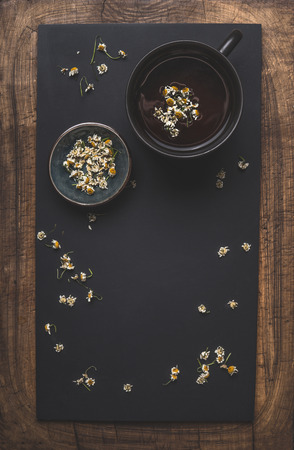 Dark chamomile tea background with cup of tea, dried chamomile flowers and honey in bowl, top view. Frame. Remedy to treat a wide range of health issues. Herbal medicine concept. Healthy hot beverage Фото со стока - 113758764
