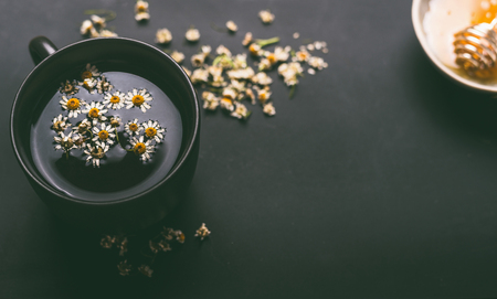 Cup of herbal chamomile tea with  dried chamomile flowers and honey on dark background, top view. Remedy to treat a wide range of health issues. Herbal medicine concept. Healing herbs.
