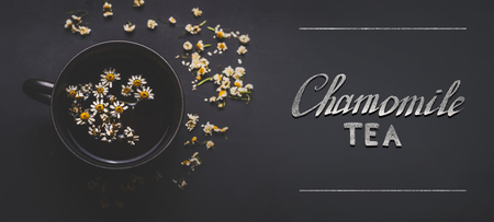 Cup of herbal chamomile tea with  dried chamomile flowers and text  on dark background, top view. Remedy to treat a wide range of health issues. Herbal medicine concept. Healing herbs .