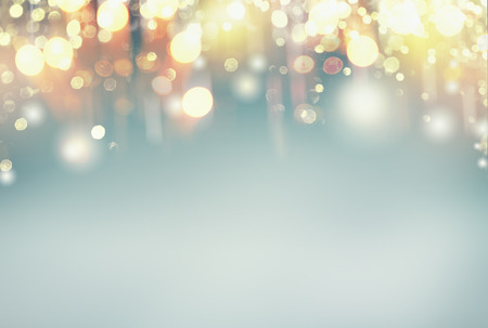 Festive holidays lighting bokeh on pastel blue background, frame with copy space