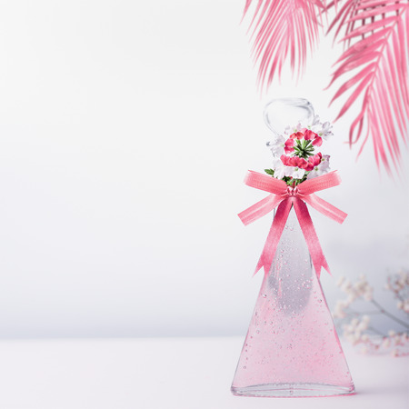 Stylized cosmetic glass bottle with pink ribbon and flowers and hanged palm leaves standing on white gray background with copy space. Skin care and beauty concept