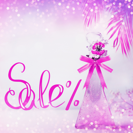 Cosmetic , Sale text lettering. Product glass bottle with in neon color with ribbon ,flowers and hanged palm leaves standing on pink background. Skin care, cosmetic shop and abstract beauty concept 写真素材