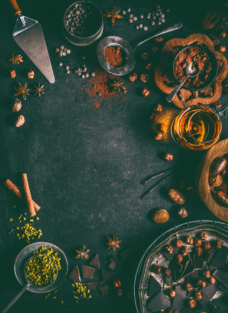 Chocolate background with various nuts and spices topping and flavoring on dark rustic background, top view, frame.  Patisserie , bakery or sweet food concept