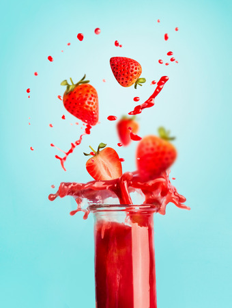 Glass of red strawberry splash summer beverage: smoothie or juice standing at blue background with copy space for your design,recipes and text. Healthy drinks concept Stockfoto