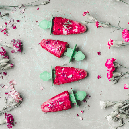 Fruits and berries ice cream . Homemade ice cream on light green kitchen table background, top view. Healthy summer desserts. Frozen juices on sticks. Vegan ice Фото со стока