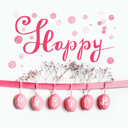 Happy Easter greeting card lettering with hanging pastel pink Easter eggs on ribbon with flowers at white wall background