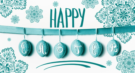 Happy Easter greeting card lettering with hanging turquoise Easter eggs on ribbon with flowers at white wall background