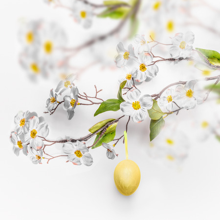 Spring blossom branches with hanging yellow Easter egg at white wall background. Stock Photo
