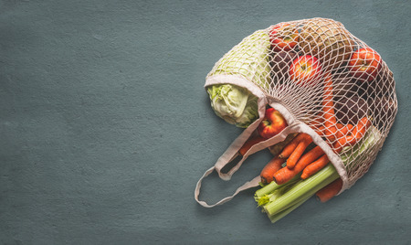 Various farm organic vegetables from local market in net string shopping bag on rustic background, top view with copy space for your design, banner. Clean and healthy food concept. Seasonal vegetable