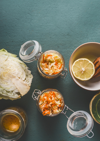 Fresh cabbage salad in glass jar for healthy lunch on kitchen table background, top view, with copy space. Vegetarian food, low-calorie vegetable eating and weight loss dieting