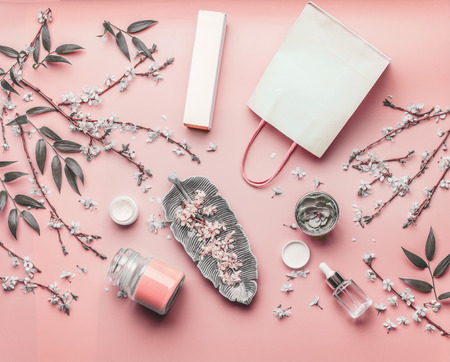 Cosmetic concept. Various facial products and paper shopping bag on pastel pink background with cherry blossom and leaves, top view, frame. Copy space for your design. Beauty blog layout. Flat lay Stock Photo - 115180662