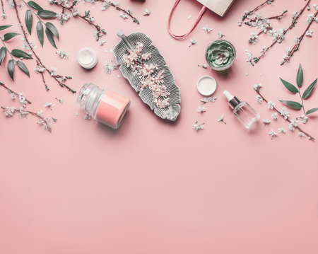 Cosmetic and skin care concept. Various facial anti-aging products on pastel pink background with cherry blossom and leaves, top view, frame. Copy space for your design. Beauty blog layout. Flat lay