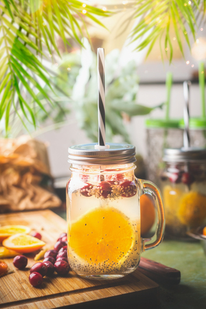 Chia seeds detox water with orange fruit slice , lemon juice and cranberries in glass jar with drinking straw on kitchen table with ingredients. Summer drinks concept. Fitness and diet nutrition