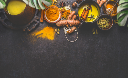 Healthy ingredients border for making turmeric milk drink with fresh turmeric roots , spices and honey on dark background. Hot winter beverage. Immune boosting remedy , detox and dieting concept . 版權商用圖片