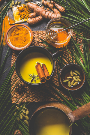 Healthy turmeric milk drink made with turmeric roots , spices and honey. Hot winter beverage. Immune boosting remedy , detox and dieting concept