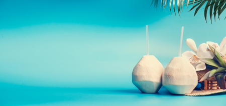Summer tropical vacation background banner with fresh tropical coconut cocktails , drinking straws and palm leaves and flowers standing on blue turquoise background. Travel and holiday concept
