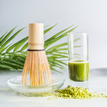 Close up of matcha espresso in glass with whisk and matcha powder on table at light background, front view with copy space. Clean, detox beverage, healthy dairy food concept. Antioxidant boost drink Banco de Imagens