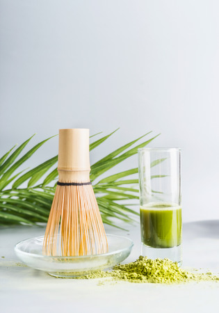 Matcha espresso in glass with whisk and matcha powder on table at light background, front view with copy space. Clean eating, detox beverage, healthy dairy food concept. Antioxidant boost drink