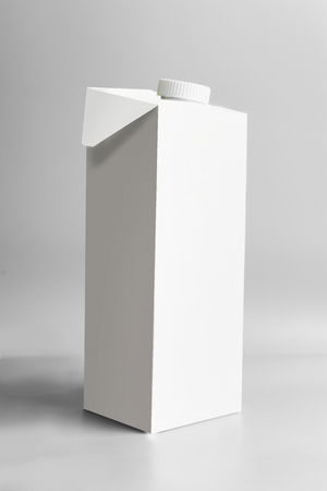 White packaging tetra-pack standing on light gray background, front view. Package branding moc-up. Empty template box milk or juice Stockfoto