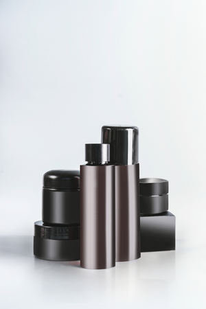 Black and brown cosmetic product jars and bottles with branding mock up, standing on light table at wall background. Snail mucin cosmetic set or charcoal cosmetics. Modern facial skin care. Copy space