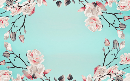 Magnolia pink blossom flowers frame at light blue turquoise background.  Floral border. Pattern of branch with flowers. Spring template or layout. Pastel color Stock Photo