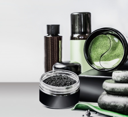 Cosmetics setting ads. Black package template with charcoal powder and green eye patches Stock Photo