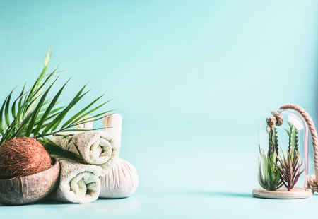 Rolled towels, compress balls with coconut, palm leaves and various succulent plants in glass at light blue