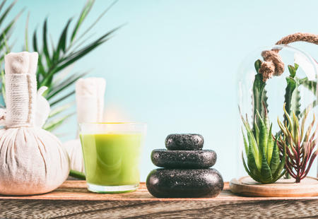 Spa concept with massage equipment:  stack of massage stones,  aromatherapy candles,  herbal stamps setting on wooden table with succulent plants at light blue Stock Photo