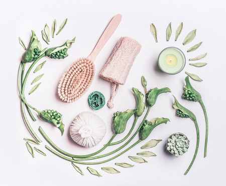 Various anti-cellulite equipment for dry massage at home on white background wit green leaves and flowers, top view. Dry brushing and skin pilling. Beauty and body care concept Stockfoto