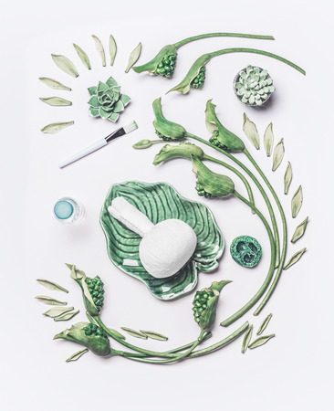 Spa composing with herbal massage stamp in green tropical bowl with leaves and flowers on white table background, top view, flat lay. Abstract beauty , natural skin care and cosmetic concept