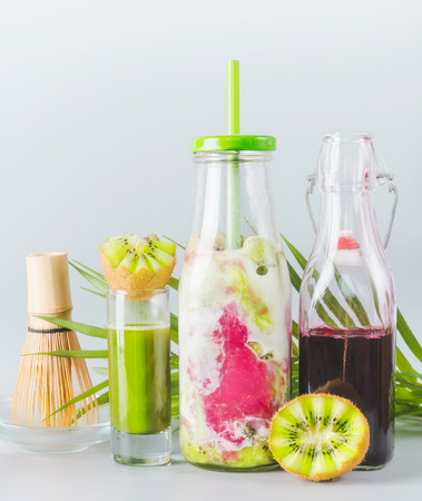 Iced Matcha fusion latte in bottle with ingredients: matcha espresso, red berries juice, kiwi fruits and milk on table with copy space. Healthy summer detox beverage concept. Matcha drink.