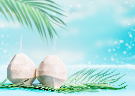 Coconut cocktails in fresh coconuts on palm leaves at sea Stock Photo