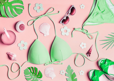 Summer flat lay. Green woman's beach accessories: swimsuit bikini , sandals, drink, sunglasses , sea shells and tropical leaves on pink background, top view. Summer holiday concept. Tropical vacation