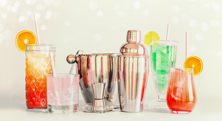 Colorful summer long drinks bar and cocktails tools in various glasses with drinking straws and citrus fruits standing at light background Stock Photo
