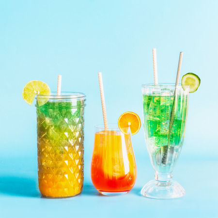 Various colorful summer refreshing lemonade long drinks with ice cubes and cocktails in glasses with paper drinking straws and citrus fruits at blue background