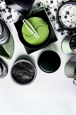 Facial cosmetic products setting in black and brown packaging. Natural cosmetics. Modern skin care with eye patches and charcoal powder on light background, top view with copy space. Beauty concept Stock Photo