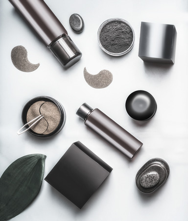 Top view of black and brown packaging of facial cosmetic products. Modern cosmetic set flat lay. Skin care with eye patches and charcoal powder. Beauty concept. Branding mock up