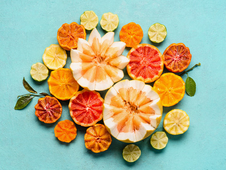 Various citrus fruits on light blue background, top view. Composing with half of orange fruits, lemon, grapefruit, mandarin, lime, clementines, pomelo and blood orange. Flat lay. Healthy food Stock Photo