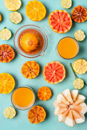 Various colorful tropical citrus fruits with juice in glasses and citrus squeezer on light blue background, top view, flat lay. Healthy drinks. Clean eating. Vitamin C concentration