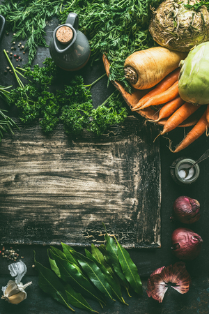 Root vegetables ingredients on dark kitchen table background with herbs and spices, top view. Copy space. Vegetarian cooking and eating concept. Healthy food